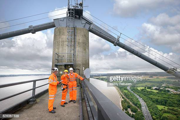 bridge workers on top of suspension bridge. the humber bridge, uk was built in 1981 and at the time was the worlds largest single-span suspension bridge - monty rakusen stock pictures, royalty-free photos & images