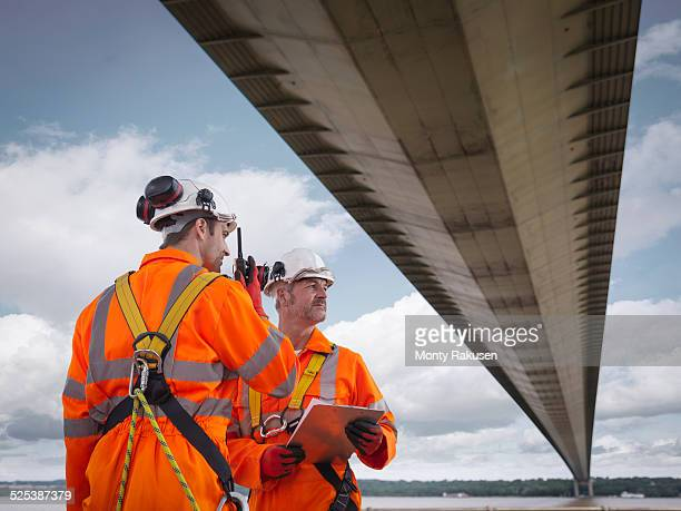 Bridge workers using walkie-talkie under suspension bridge. The Humber Bridge, UK was built in 1981 and at the time was the worlds largest single-span suspension bridge