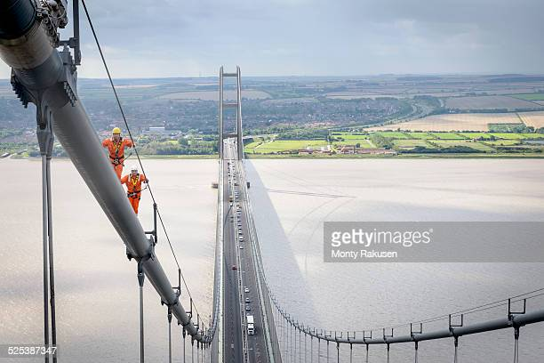 Bridge workers walking on cable of suspension bridge. The Humber Bridge, UK was built in 1981 and at the time was the worlds largest single-span suspension bridge