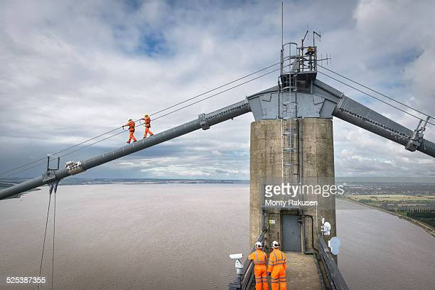 bridge workers walking on cable of suspension bridge. the humber bridge, uk was built in 1981 and at the time was the worlds largest single-span suspension bridge - monty rakusen stock photos and pictures