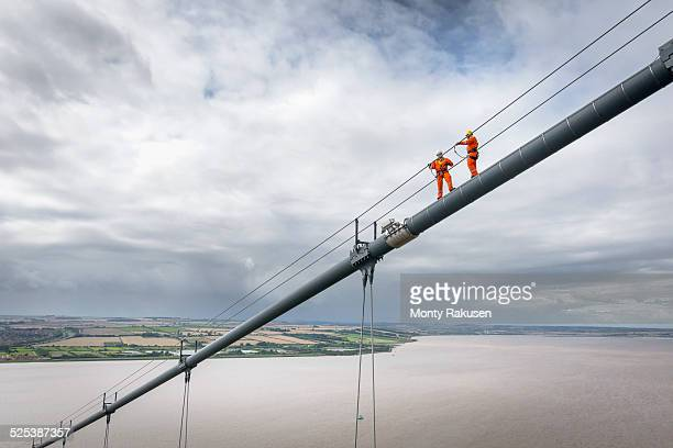 Bridge workers working on cable of suspension bridge. The Humber Bridge, UK was built in 1981 and at the time was the worlds largest single-span suspension bridge