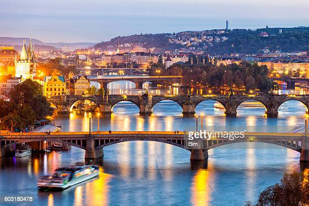 bridges on vltava river at dusk in prague, czech republic - charles bridge stock photos and pictures