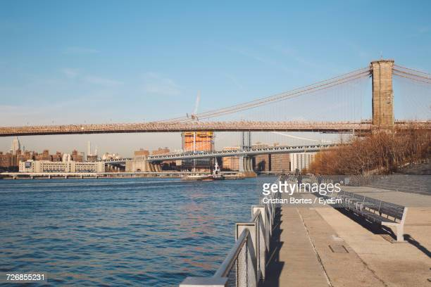 bridges over east river and promenade against clear blue sky - bortes stock-fotos und bilder