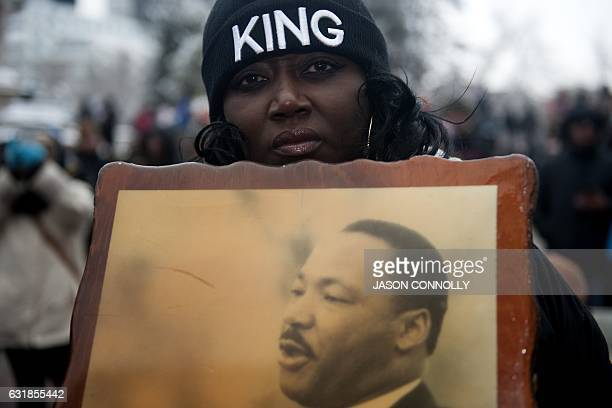 TOPSHOT Bridget Johnson holds a picture of the late Dr Martin Luther King Jr while marching in Denver Colorado during Denver's Martin Luther King Jr...