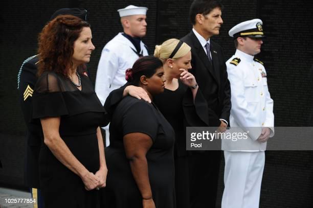 Bridget McCain and Meghan McCain hug while US Secretary of Defense James Mattis General John Kelly White House Chief of Staff and Cindy McCain wife...