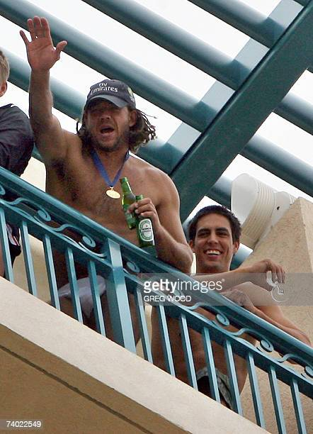 Australian cricketer Andrew Symonds holds bottles of beer as his teammate Mitchell Johnson looks on while they stay in their hotel balcony in...
