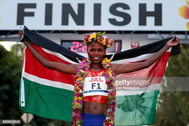 Bridgid Kosei of Kenya poses with a flag after winning the Women's division of the Honolulu Marathon 2017 on December 10 2017 in Honolulu Hawaii
