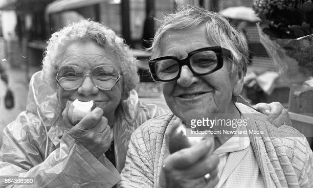 Bridie Conlon and Elizabeth Byrne enjoying an apple each as they mark National Apple Day in Moore Street Dublin circa October 1989
