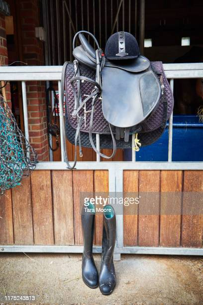 bridle, saddled and ridding boots in stables - riding boot stock pictures, royalty-free photos & images