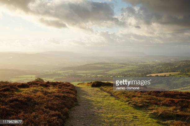 bridleway on hilltop with coutryside views below at sunset. - rural scene stock pictures, royalty-free photos & images
