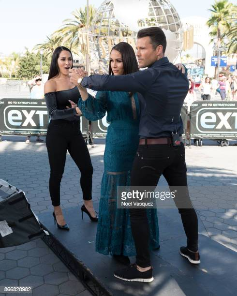 Brie Bella dances with Mark Wright as Nikki Bella watches at Extra at Universal Studios Hollywood on October 26 2017 in Universal City California