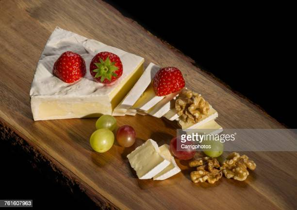 brie cheese with walnuts, grapes and strawberries - brie stock photos and pictures