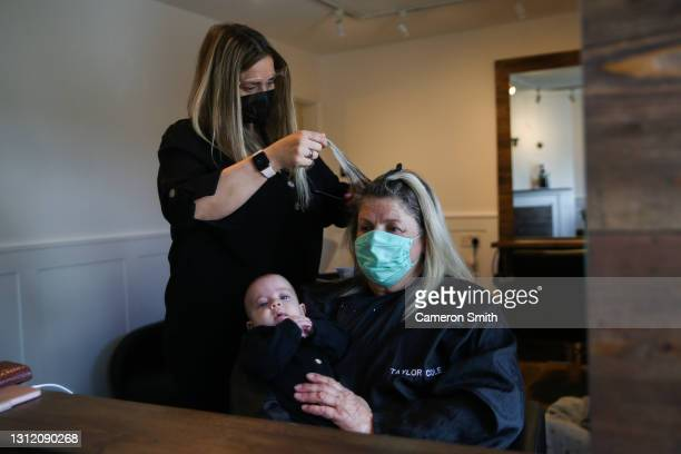 Brie Hoare, owner of Blake Beaux Salon, cuts Kerry Harris' hair while she holds baby Blake at Blake Beaux salon on April 12, 2021 in Truro, England....