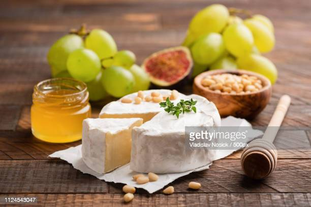 brie or camembert cheese with grapes, honey, figs - brie stockfoto's en -beelden
