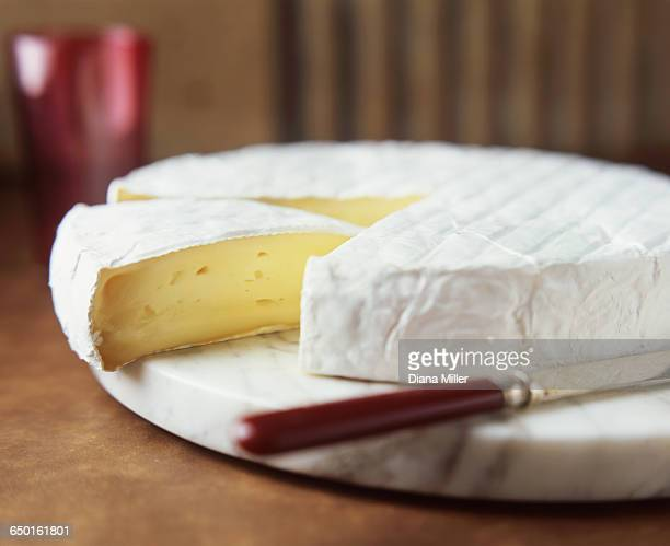 Brie round with cheese knife on marble cutting board
