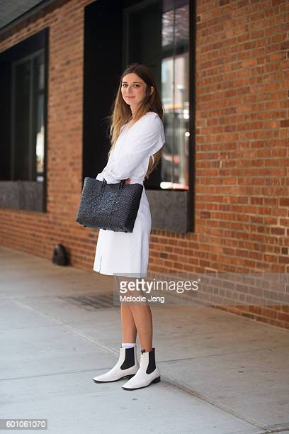 Brie Welch of Garance Dore wears all white with a black purse at the Brock Collection show at Milk Studios on September 8 2016 in New York City