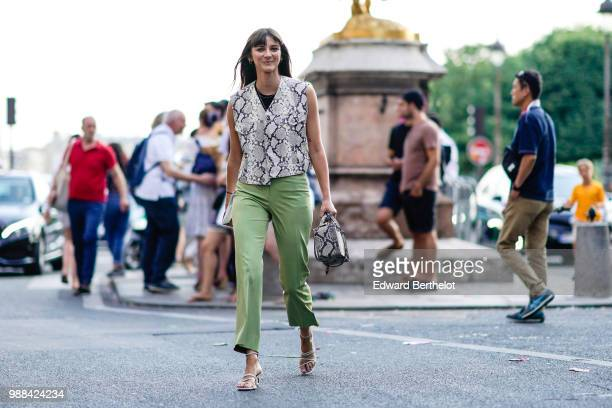 Brie Welch wears a white snake print sleeveless jacket green pants outside the Miu Miu Cruise Collection show outside the Hotel Regina in Paris on...