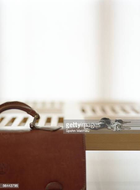 Briefcase and keys on table