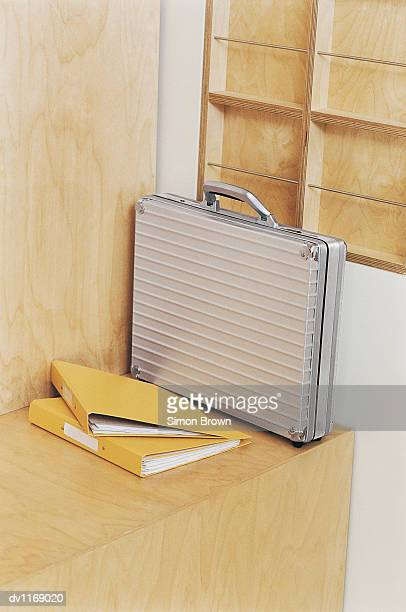 Briefcase and Two Ring Binders on a Wooden Bench in an Office