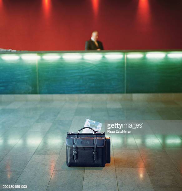 Briefcase holding newspaper, sitting in middle of hotel lobby