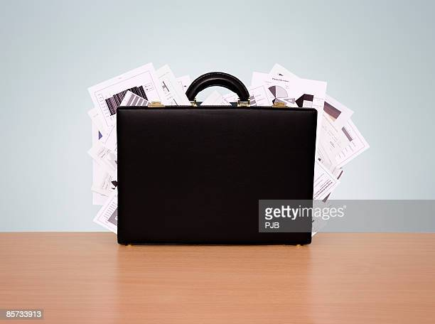 Briefcase overstuffed with papers
