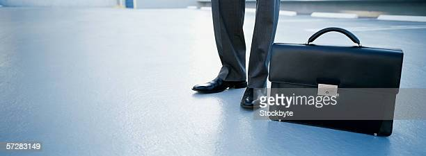briefcase standing beside businessman's feet