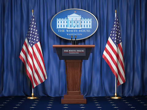 Briefing of president of US United States in White House. Podium speaker tribune with USA flags and sign of White Houise. Politics concept. 1021174468