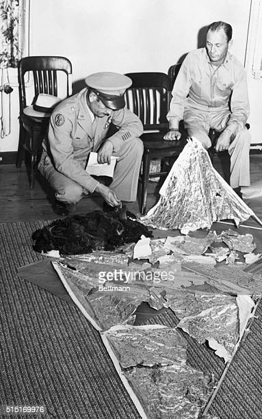Brig General Roger M Ramey Commanding General of 8th Airforce and Col Thomas J Dubose 8th Airforce Chief of Staff identify metallic fragments found...