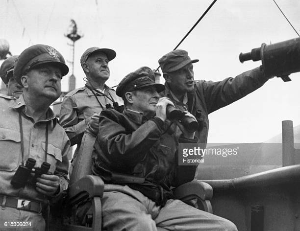 Brigadier General Courtney Whitney; General Douglas MacArthur, Commander in Chief of U.N. Forces; and Major General Edward M. Almond, observe the...