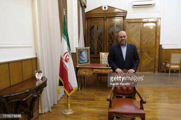 Brigadier General Hossein Dehghan adviser to the supreme leader of Iran in civilian clothing stands in front of a framed portrait of Qassem Soleimani...