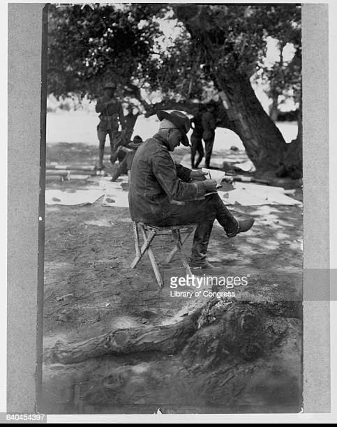Brigadier General Pershing writes under a shady tree during the Punitive Expedition to Mexico he led to attempt to capture Pancho Villa. Near Casas...