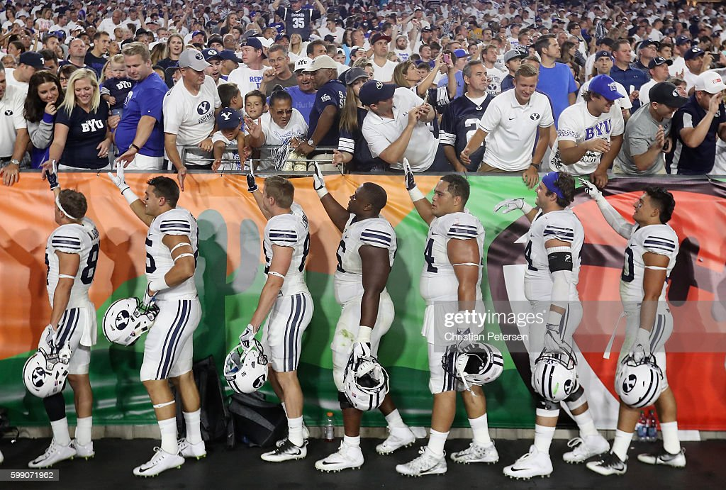 Brigham Young Cougars players high five fans following the college football game against the Arizona Wildcats at University of Phoenix Stadium on September 3, 2016 in Glendale, Arizona. The Cougars defeated the Wildcats 18-16.