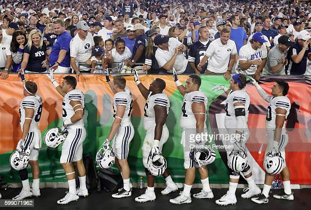Brigham Young Cougars players high five fans following the college football game against the Arizona Wildcats at University of Phoenix Stadium on...