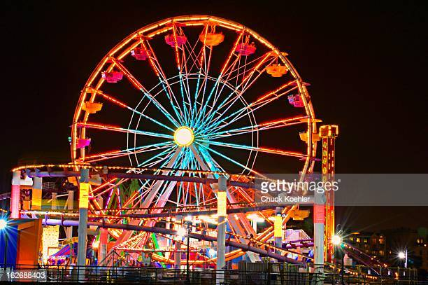 Bright and colorful image of the Ferris Wheel and Roller Coaster on the Santa Monica Pier. Night shot with lots of neon lights and brightly painted...