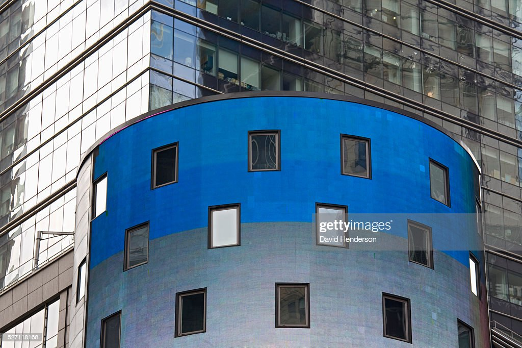 Bright blue and grey cylindrical building in front of a reflective glass skyscraper : Stock Photo