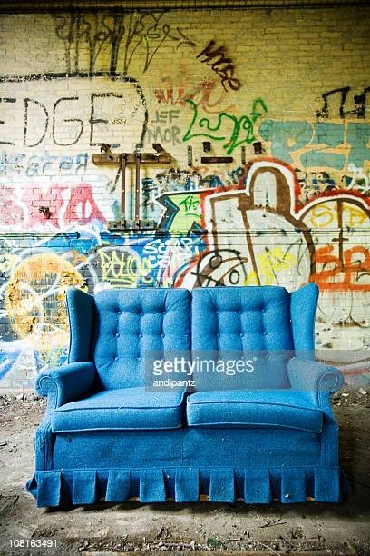 Bright Blue Couch Against Cement Wall of Graffiti