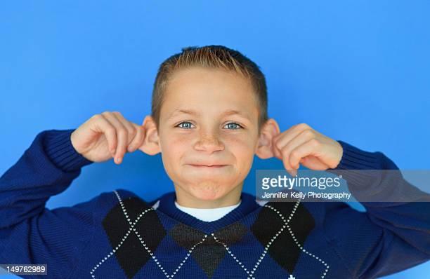 Bright blue eyed boy making monkey face