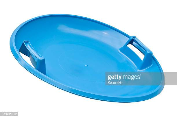 A bright blue round plastic toboggan on a white background
