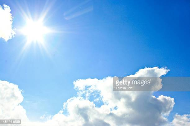 Bright blue sky with clouds and sun flare