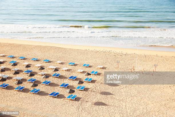 Bright blue sun beds on empty beach
