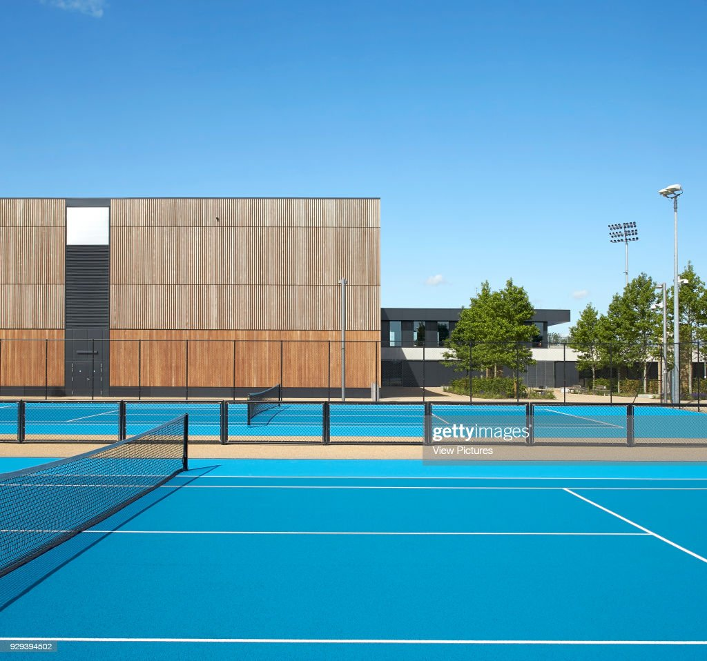 Bright blue tennis court and timber clad facade  Eton Manor