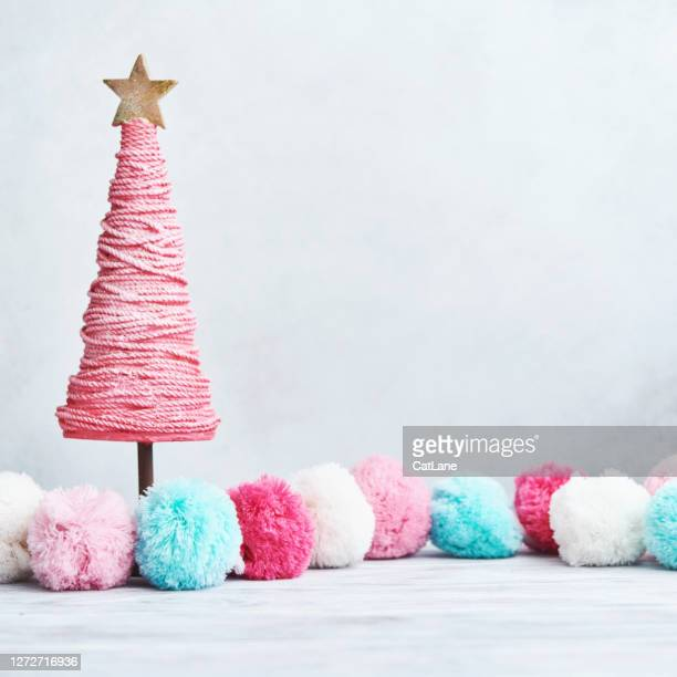 bright christmas background with pastel pompoms and pink christmas tree on white wood - pom pom stock pictures, royalty-free photos & images