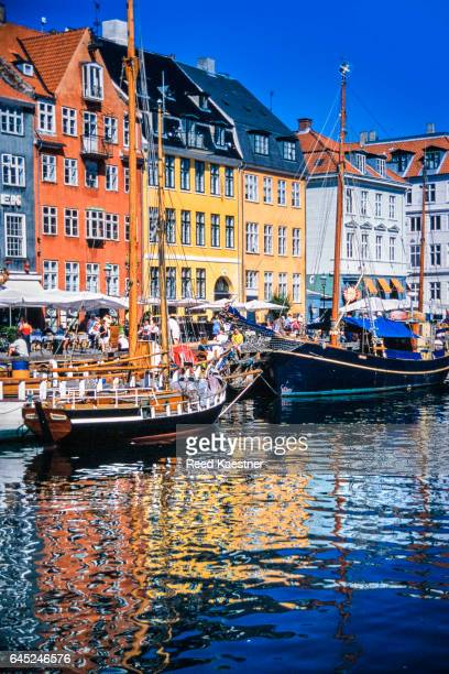 Bright colored buildings reflect in the old harbor at Copenhagen, Denmark.