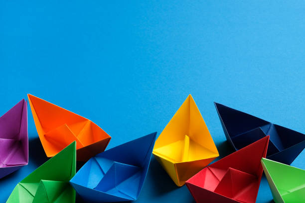 Bright Colorful Paper Boats On A Blue Background, handmade. The concept of competition in business and team, leadership. Copy space.