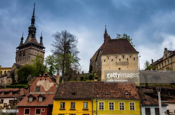 Bright coloured traditional architecture and clock tower in Sighisoara old town, Transylvania, Romania