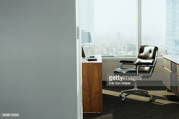 bright corner office space with desk and chairs - niemand stock-fotos und bilder