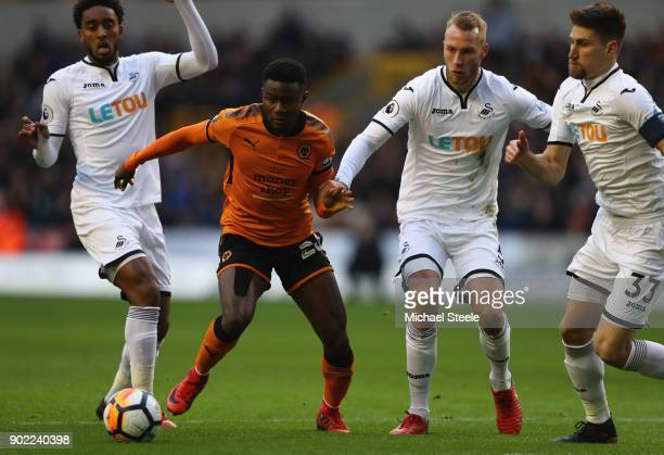 Bright Enobakhare of Wolves is surrounded by Leroy Fer Mike Van Der Hoorn and Frederico Fernandez of Swansea during the Emirates FA Cup Third Round...