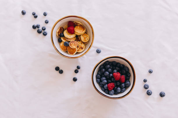 Bright food photography of two ceramic bowls filled with blueberries, raspberries and mini pancakes