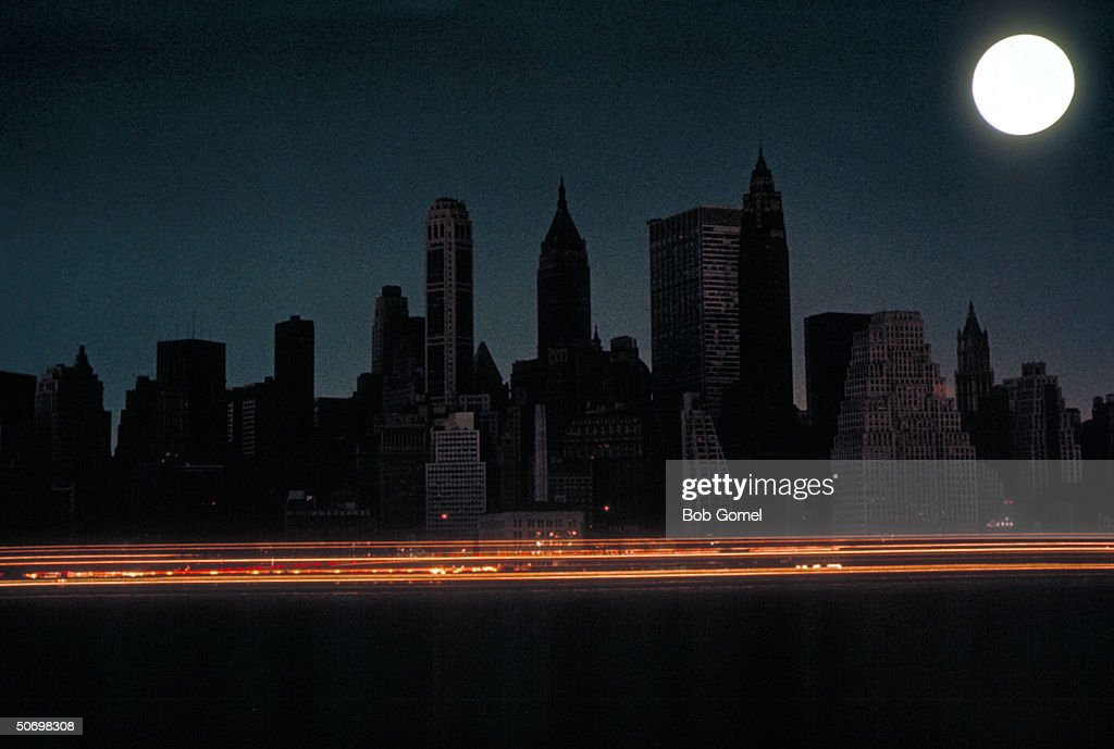 Bright full moon over darkened New York City skyline during massive East Coast blackout affecting 80,000 square miles.