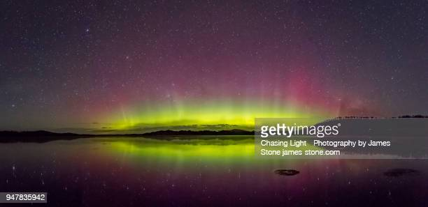 bright green display of the aurora australis or southern lights with reflection in water - aurora australis stock pictures, royalty-free photos & images